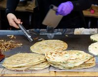 A street food stall offers pancakes with spring onions cooked on a hot griddle