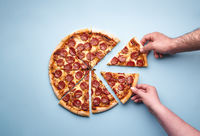 Taking pizza slices above view. Couple eating pizza