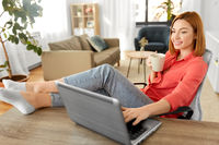 woman with laptop drinking coffee at home office
