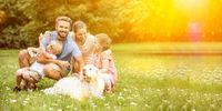 Glückliche Familie mit Kinder und Hund im Garten