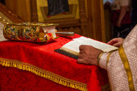 A priest holding the Bible at a christian ritual. Christian celebraton service concept.