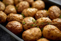 Close up on homemade roasted whole potatoes in jackets. With butter, rosemary and thyme.