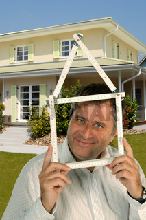 Mann mit Zollstock vor einem Haus