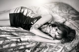 Young beautiful woman lying on a bed