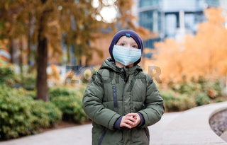 Boy in a medical mask. Autumn time and mask. Child with protection. Plac Europejski in Warsaw.
