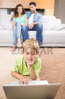 Cute little boy using laptop on the rug with parents sitting sofa