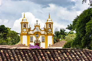 View of historic church between roofs and vegetation in Tiradentes city