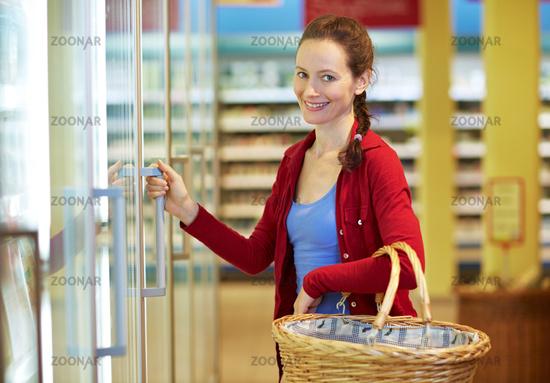 Frau im Supermarkt am Kühlregal