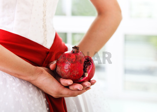 Pomegranate in hands of a bride