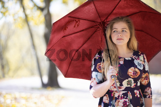 Beautiful young woman in an autumn park with an umbrella.