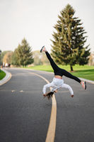 Woman athlete leaping somersault on the road, doing exercises outdoors.