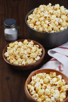A pot of fresh popped popcorn and two bowls on a rustic wood table with salt shaker. Vertical format.