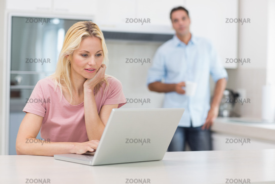 Woman using laptop with man drinking coffee in kitchen
