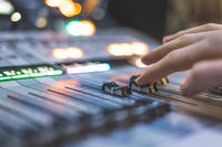 Sound recording studio mixer desk: sound engineer is operating a professional music production