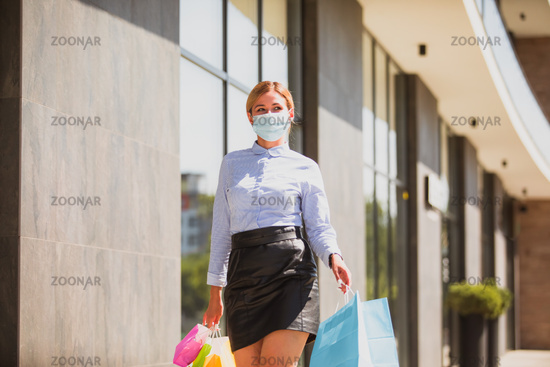 Young woman in protective mask while shopping