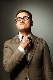 Confident nerd in eyeglasses adjusting his bow-tie