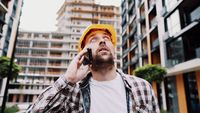 Portrait of young handyman making call while standing at construction area. Engineer talking on the phone on a construction site. Builder in helmet control according to plan by mobile phone