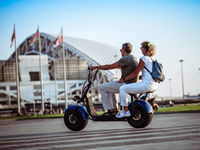 Man and woman on two-seater electric scooter