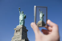 Personal perspective of tourist photographing Statue of Liberty with digital camera new york city ne