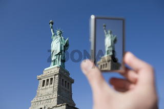 Tourist photographing Statue of Liberty with digital camera