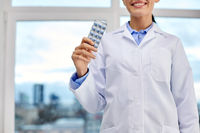 smiling female doctor with pills at medical office
