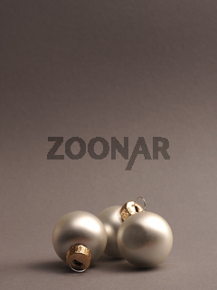 Silver vintage Christmas baubles on a grey background