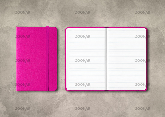 Pink closed and open lined notebooks on concrete background