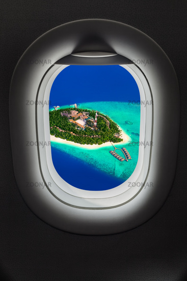 Tropical island at Maldives in airplane window