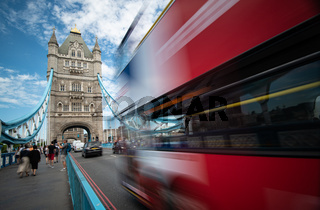 People walking and red traditional London bus crossing the famous London Tower bridge