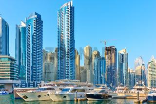 Yachts and boats neat towers of Dubai Marina