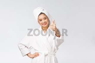 Beautiful asian woman perfect skin showing thumbs up isolated on white background.