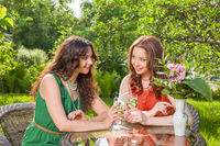 Two young women enjoy drink at backyard garden. Friends meeting outdoors