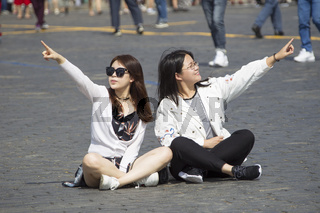 Russia, Moscow, July 29, 2018. Red Square. Young girls are sitting on the asphalt. Tourists point to landmarks