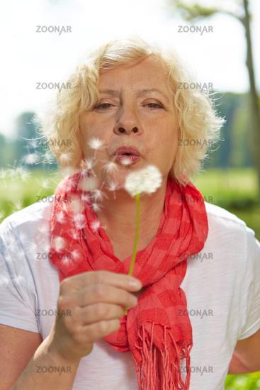 Seniorin pustet Pusteblume im Sommer