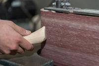 Craftsman works with belt grinder - close up carpenter in workshop