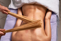 Male masseur doing Japanese massage with bamboo sticks on beautiful naked woman body in the spa salon. Beauty treatment concept.