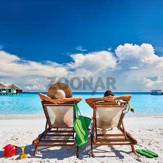 Couple in sun beds on a tropical beach
