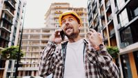 Angry builder, dissatisfied with deadline of work, swears at stress while talking to foreman on phone background of construction site. Wrathful architect, construction engineer talking on cell phone