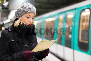 Lady waiting on subway station platform.
