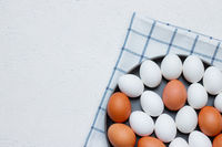 chicken eggs on a checked kitchen towel on a light table. concept of farm products and natural food. Article about home products. Fresh chicken eggs .