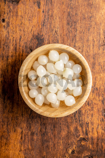 Pickled mini baby onions in wooden bowl.