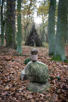 A stone cairn in the woods with a wooden stack of branches in the background