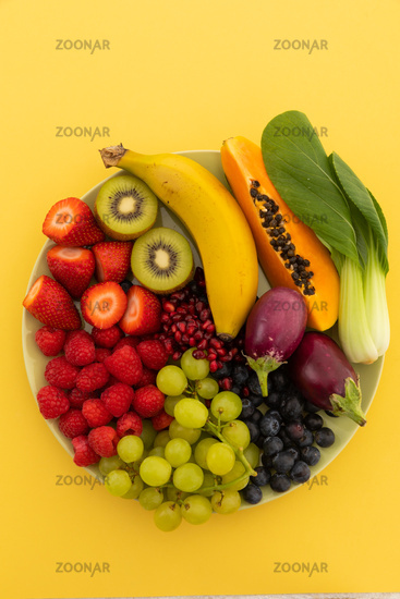 High angle view of bowl of banana, berries, grapes and baby aubergines