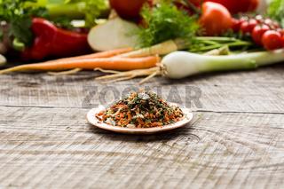 Handmade seasoning on ceramic plate, vegetables on background, blured