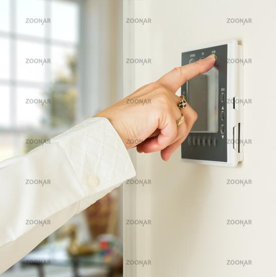 Caucasian lady pressing modern thermostat