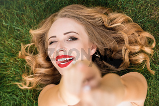 Caucasian pretty woman with curly black hair lying on the grass in the park. Smile and calm. portrait of Caucasian woman with blond hair spending day at nature