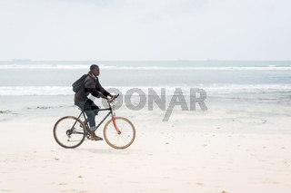 African man riding bike on tropical beach