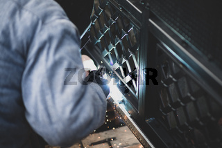 Welder welds the steel gear racks to gate before setting up automated gate operator. Professional service of installation and maintenance of automatic cantilever sliding gate.