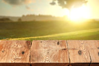Rough wooden table on natutal rural sunset landscape a for display and montage your products.