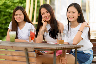 Three happy young Asian women as friends having drinks together at the coffee shop outdoors